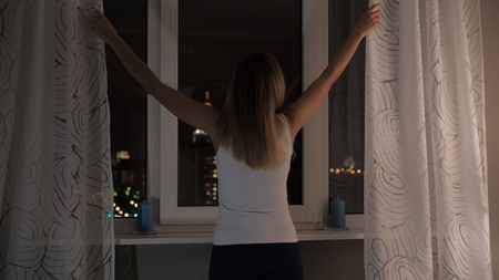 Woman Stands At The Windows At Night Looking At Street Lights, Curtains Stok Fotoğraf