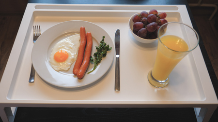 Table Breakfast Of Scrambled Eggs With Sausages, Juice, Fruit