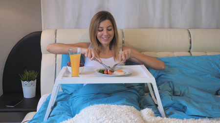 Woman Eating Breakfast Sausages With Fried Eggs On The Table, Lying In Bed