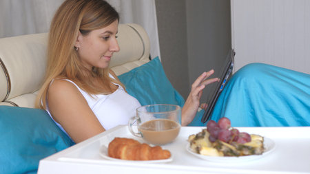 Young Woman With Laptop Eating Breakfast In Bed At Home And Drinking Coffee.