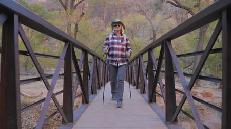 Active Woman Hiking Goes Through a River Bridge In Zion Park USA