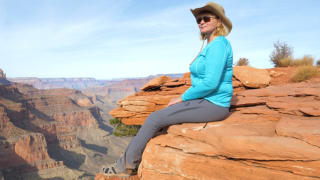 Woman Tourist Sitting On Rock Dangling Her Legs, And Admires Views Grand Canyon