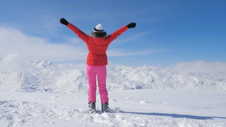 A Stylish Skier Woman On Peak Mountain, Raises Hands Up