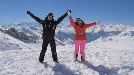 Happy skiers couple stands on the mountain peak and rises their hands Stok Fotoğraf