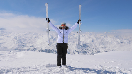 Happy Woman raises her downhill skis on the mountaintop