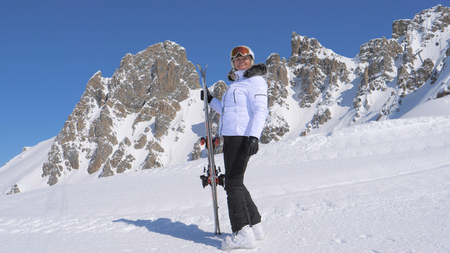 Woman Skier Stands On The Side Of A Mountain Holding Skis