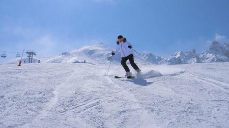 A Woman Skier Carving Go Down The Ski Slope Of The Mountain