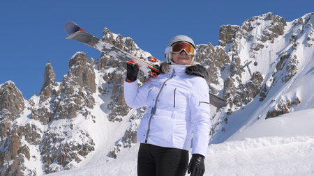Woman skier with skis on her shoulder admires beauty of nature in the mountains Stok Fotoğraf