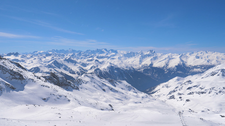 A Breathtaking Panorama of the Snowy Mountains and Skiers