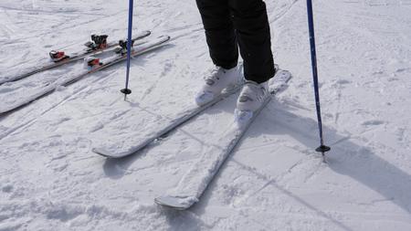 A Skier Puts On His Downhill Ski On White Ski Boots Stok Fotoğraf