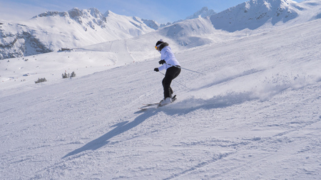 Sporty Woman Skier Professionally Carving Down The Slope In The Mountains