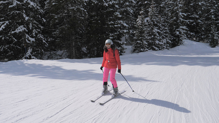 Sporty young woman skis down the slope in the mountains of the Alps