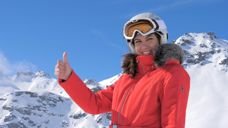 Young Pretty Woman Smiles and Gives a Thumbs Up a Snowy Mountain Background Stok Fotoğraf