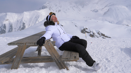 Woman Skier Pleasure to Relax in the Mountains on a Sunny Day Sitting on Bench