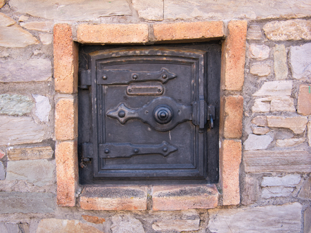 Iron door from an old oven outside on the facade with stones