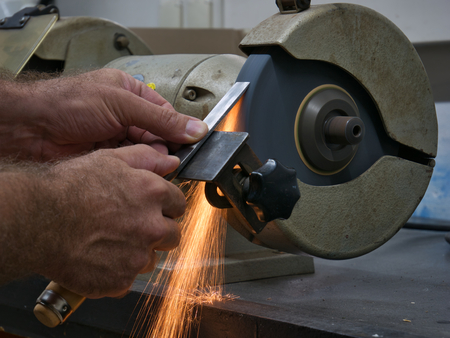 Sparking when sharpening with an electric double grinding bock on a workbench Stockfoto