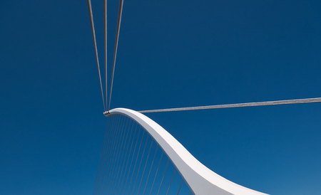 White bridge pillar stretched with steel ropes and blue sky in the background