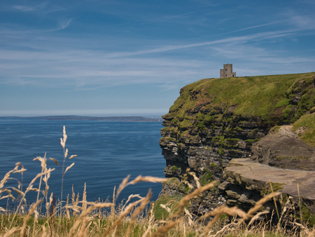 View of the cliff with rocky outcrop and the tower of the Cliff of Moher in Ireland