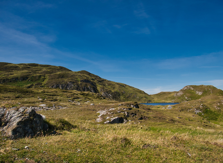 A small lake and green meadows in the mountain landscape of Croaghlin at Bunglass point Stock Photo