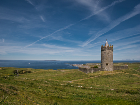 Green meadow and the tower of Doonagore Castle with the Atlantic Ocean in the background Stock Photo