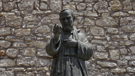 A statue of San Pio in front of a stone facade in Erice in Sicily