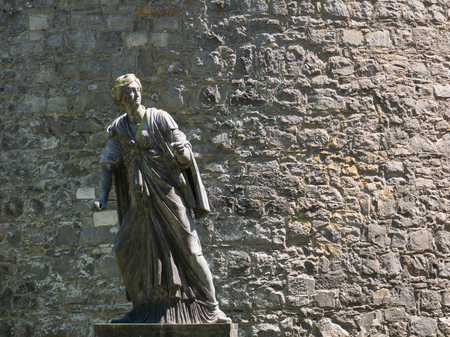 The statue of a woman in Kilkenny in front of a stone wall in the sunshine