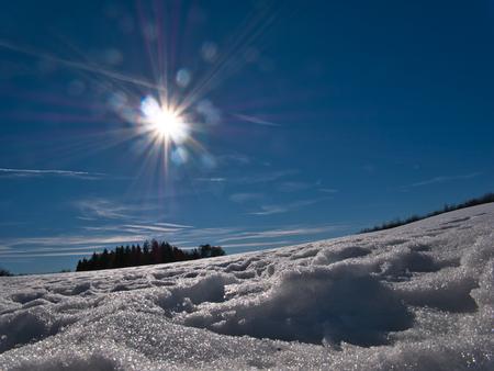 Intensive Sonnenstrahlen und der glitzernde Neuschnee in den Bergen