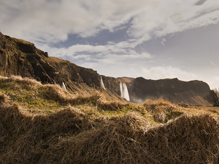 Small grassy hill with several waterfalls in the background