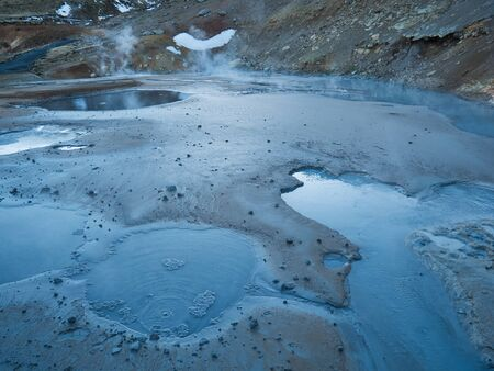 Mud hole in active geothermal area of Iceland at dusk Imagens