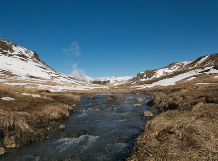 A stream with warm thermal water in Reykjadalur in March