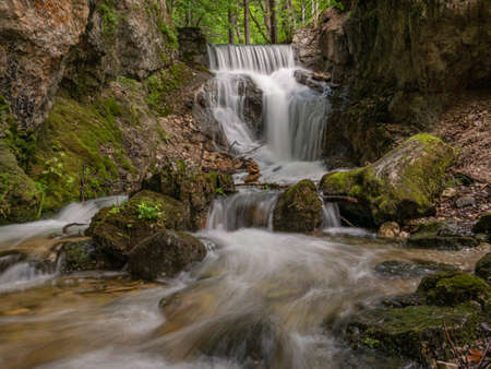 Long exposure of beautiful waterfall with small cascades in forest