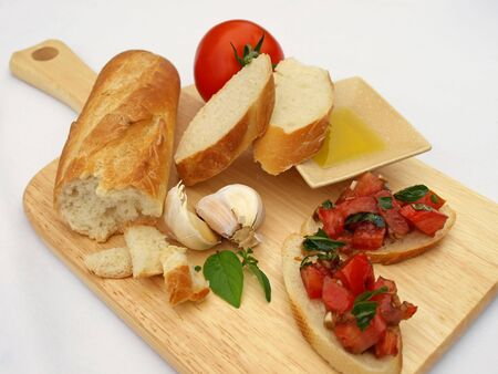 Cutting board topped with bruschetta and ingredients