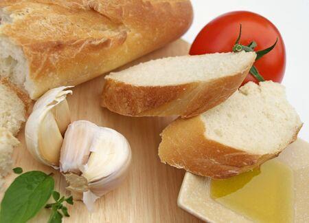パン、オリーブ オイル、木製のまな板にトマトを含む地中海の食材