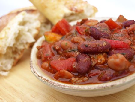 Serving of chili with beans, tomatoes and bread photo