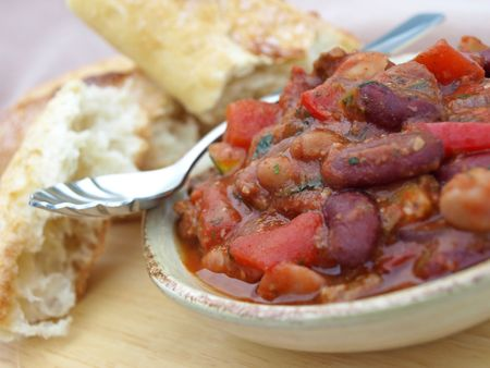 Bowl of chili with bread and spoon Stock Photo