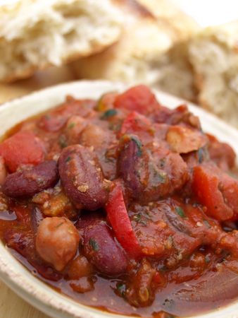 Bowl of chili with beans and tomatoes, served with bread