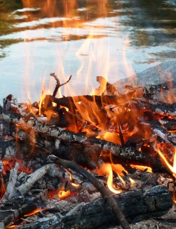 Outdoor fire burning near a lakefront