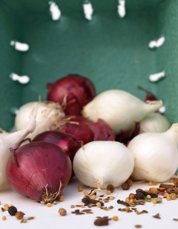 Onions and spices spilling out of basket Stock Photo