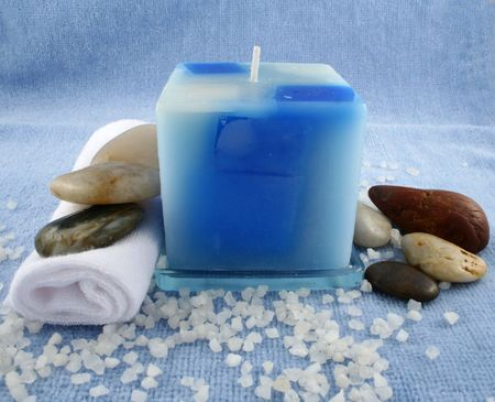 A blue candle, a facecloth, some bath crystals and some stones Stock Photo