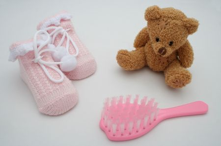 neonate: A pair of pink  booties, a brush and a bear Stock Photo