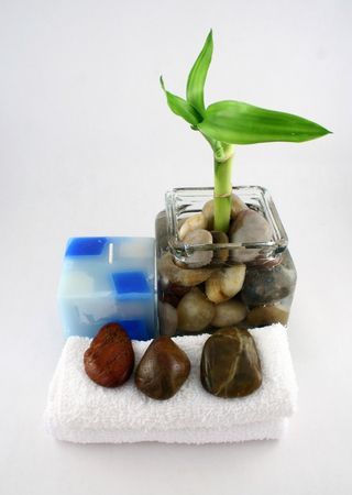 A bamboo plant, candle, towels and stones Stock Photo