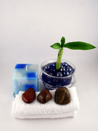 A bamboo plant, some facecloths, stones and a candle
