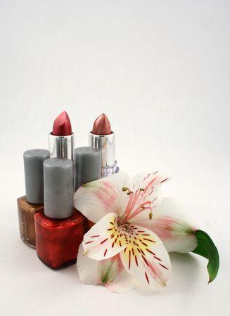Lipstick, nail polish and a lily Imagens