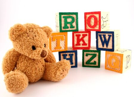 A teddy bear and some wooden blocks photo