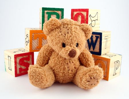 A teddy bear in front of some wooden blocks photo