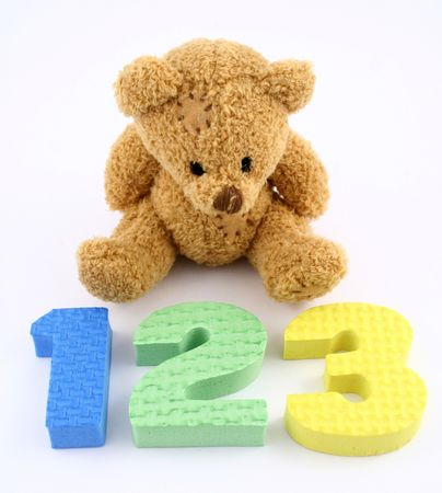 A teddy bear and some foam numbers photo