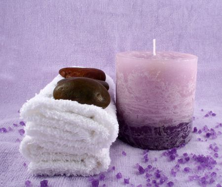 A purple candle, some towels, some stones and some bath crystals Stock Photo