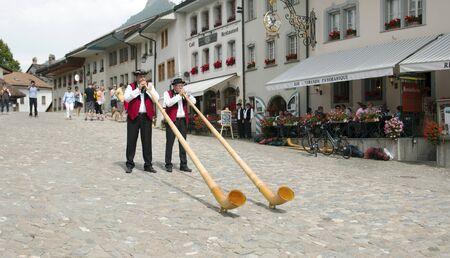 alphorn: Gruyere, Switzerland - July 19, 2014. Swiss musicians play the folk national musical instrument alphorn in the Gruyere village. Editorial
