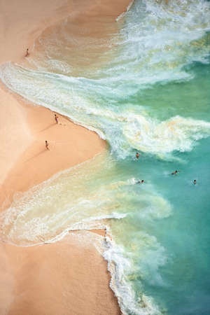 View from above, stunning aerial view of some tourists playing, sunbathing and swimming on a beautiful beach bathed by a turquoise sea during sunset. Kelingking beach, Nusa Penida, Indonesia.
