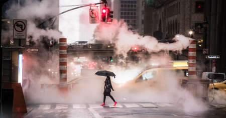 A woman wearing red high heels is crossing the 42nd street in Manhattan during the Covid-19 outbreak. Manhattan, New York City, United States.